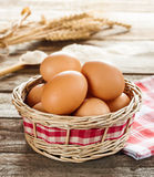 Eggs in a wicker basket on vintage wood table. Eggs in a wicker basket on an old vintage planked wood table, wheat bunch and flour as background. Rural or rustic stock image