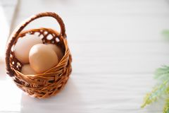 Eggs in a wicker basket on a white wooden background.  Royalty Free Stock Photography