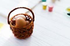 Eggs in a wicker basket on a white wooden background.  Royalty Free Stock Image