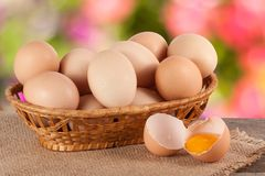 Eggs in a wicker basket on a wooden board with blurred garden background.  royalty free stock image
