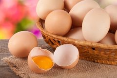 Eggs in a wicker basket on a wooden board with blurred garden background.  royalty free stock photo