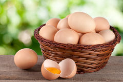 Eggs in a wicker basket on a wooden board with blurred garden background Stock Images