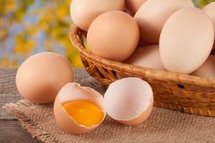 Eggs in a wicker basket on a wooden board with blurred garden background.  stock photography