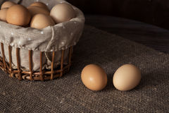 Eggs in a wicker basket on a wooden table Royalty Free Stock Images