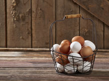 Eggs In Wire Basket. On wood Royalty Free Stock Images