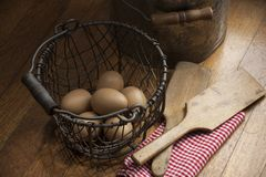Eggs in a Wire Basket on a Wooden Background Royalty Free Stock Image