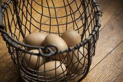 Eggs in a Wire Basket on a Wooden Background Stock Images