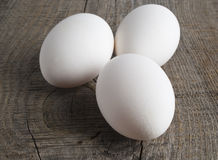 Eggs on wooden background. Three white eggs on the wooden background Royalty Free Stock Photo