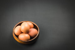 Eggs in wooden bowl. Eggs in wooden bowl on black plywood background Stock Photo