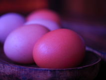 Eggs on a wooden bowl. Eggs of different shades of brown and white in a softlight on a wooden bowl with a vintage purple colouration Stock Photo