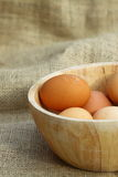 Eggs wooden bowl hessian A. Eggs in a wooden bowl on hessian royalty free stock images