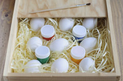 Eggs in a wooden box. Paints and brush for decorating. White eggs on a soft substrate in a wooden box. Paints and brush for decorating. Happy Easter Stock Image