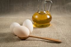 Eggs with a wooden spoon on the table with a bottle of sunflower oil on a background of linen texture. Vintage still life Royalty Free Stock Photo