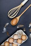 Eggs, wooden spoon, whisker and feathers. Kitchen utensil for cake, pastry or cookies on backboard background. Top view stock images