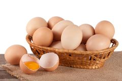 Eggs on a wooden table in a wicker basket on a white background.  royalty free stock images