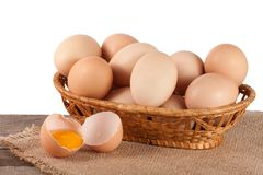Eggs on a wooden table in a wicker basket on a white background.  stock image