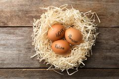 Eggs with words PENSION, RETIRE and 401k in nest. On wooden background, top view stock photography