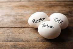 Eggs with words PENSION, RETIRE and 401k on wooden background. Space for text royalty free stock photos