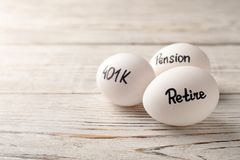 Eggs with words PENSION, RETIRE and 401k on wooden background. Space for text royalty free stock image