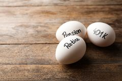 Eggs with words PENSION, RETIRE and 401k on wooden background. Space for text royalty free stock images