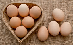 Eggs in a Woven Straw Basket on a burlap Sacking Royalty Free Stock Images