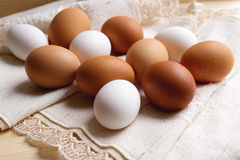 Eggs wrapped in cloth on wood table. White and brown eggs wrapped in cloth on wood table Royalty Free Stock Image
