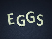 Eggs written with colorful wooden letters on a blue background Stock Photo