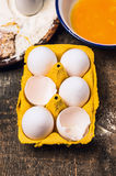 Eggs in yellow package on old wooden table Stock Images