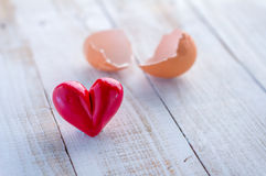 Eggshel et coeur sur le fond en bois blanc Image libre de droits