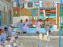 Egipscy mężczyzna rzeźbi błyskotki sprzedawać turyści wewnątrz z colourful malowidło ścienne ścianą fotografia royalty free