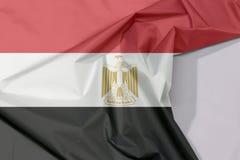 Egipt tkaniny flaga zagniecenie z biel przestrzenią i krepa zdjęcia stock