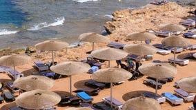 Egipto, playa con los paraguas y los sunbeds en el Mar Rojo cerca del arrecife de coral almacen de metraje de vídeo