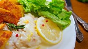 Eglefino al forno del limone con le patate fritte Sause del limone, Fotografie Stock