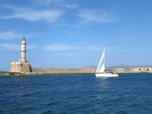 Żeglować Białego jacht blisko latarni morskiej na Błękitnym morzu egejskim, Crete wyspa, Grecja Zdjęcia Royalty Free
