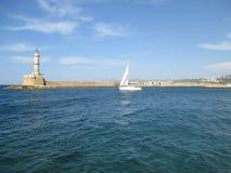 Żeglować Białego jacht blisko latarni morskiej przy Starym Weneckim schronieniem Chania, Crete wyspa, Grecja Obraz Stock