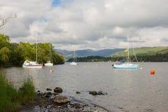 Żeglowanie łodzie na jeziorze z górami w tle Fotografia Stock