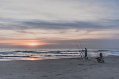Egmond-aan-Zee, Netherlands - 09-24-2016: Angling on the North S. Egmond-aan-Zee, Netherlands - 09-24-2016: Sea angling fisherman at sunset at the North Sea stock photography