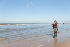 Fisherman with double catch -at the Sea fishing competition along the Northsea shore. Egmond-aan-Zee, Netherlands - 2016-04-10: Fisherman with double catch on royalty free stock photos