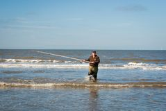 Fisherman walking back to the shore. Sea fishing competition along the Northsea shore royalty free stock image