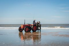 Egmond-aan-Zee, Netherlands - 2016-04-10: 3 men of the organisation with a red tractor on the beach. During the Sea fishing competition along the Northsea shore royalty free stock image