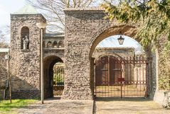 Entrance gates to the cloister garden of the Lioba cloister. Egmond-Binnen, Netherlands - 04-10-2016: Brick arched entrance gates and gatebuilding to the stock images