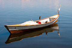 Egret on a fishing boat. Egret resting on a smal fishing boat, with calm waters Royalty Free Stock Photos