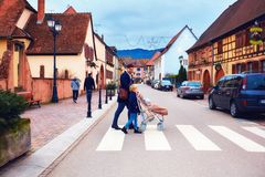 EGUISHEIM, ALSACE, FRANCE - DECEMBER 24, 2017: cute family crossing the street of medieval village. EGUISHEIM, ALSACE, FRANCE - DECEMBER 24, 2017: cute family Royalty Free Stock Images