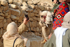 Egypt. A woman takes a picture with her mobile phone to somebody mounted on a camel, at the pyramids in Cairo, Egypt Stock Photo