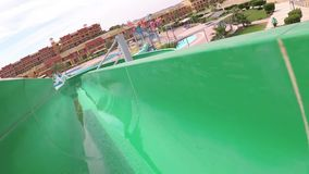 Egypt, Abu Dabb - March 16, 2019: a person slides down a slide in a stream of water and falls into a pool of water. Egypt, hotel stock video footage