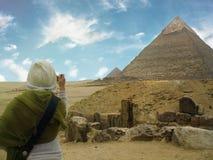 Egypt cairo giza La giovane donna fa una foto delle piramidi Sta stando di nuovo alla macchina fotografica Il cielo blu con nuvol immagini stock