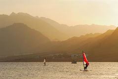 Egypt. Dahab. Windsurfing at sunset. Man and woman makes windsurfing by the calm waters of the Red sea Stock Photography