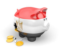 Egypt economy and finance concept for unemployment, spending, and national debts. Piggy bank bearing the Egyptian flag, spilling coins out a hole in the side Royalty Free Stock Photo