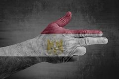 Egypt flag painted on male hand like a gun. On concrete background royalty free stock photo