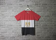 Egypt flag on shirt and hanging on the wall with brick pattern wallpaper royalty free stock image